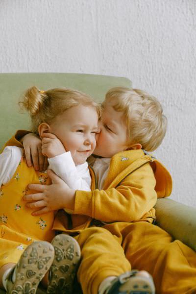 Zwei kuschelnde Kinder auf der Couch tragen Sweatshirts mit Bündchen und Kinderschuhen
