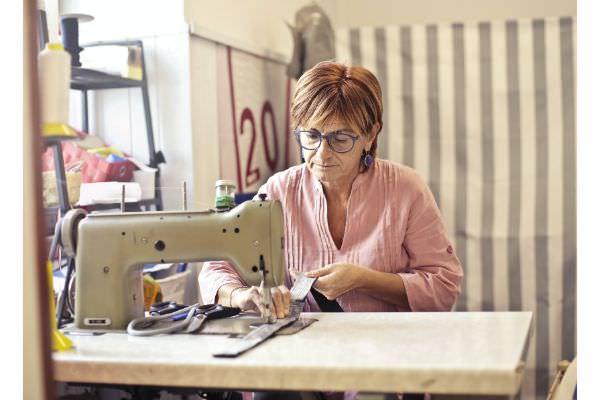 Schneiderin sitzt an ihrer Nähmaschine und fertigt Bündchen als Schlauchware an