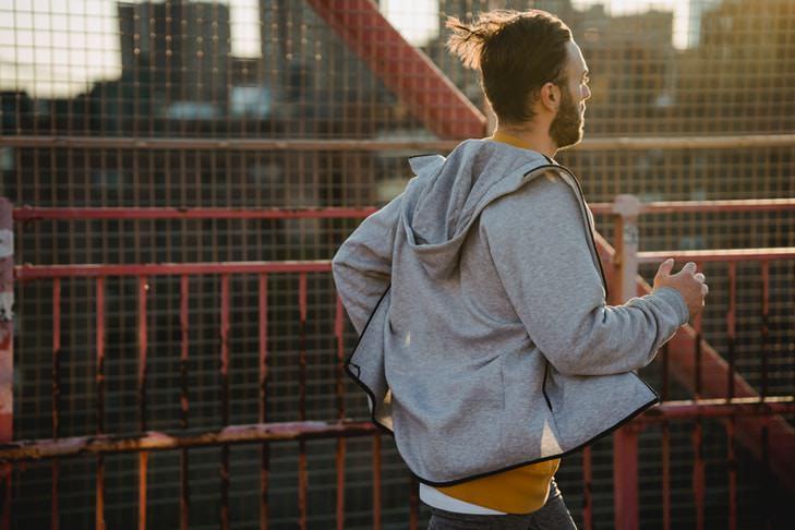 Ein Mann mit einer grauen Sweatjacke joggt über eine Brücke.