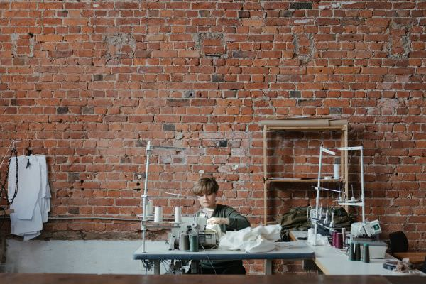 Eine Näherin verarbeitet Jersey Stoff an ihrer Nähmaschine
