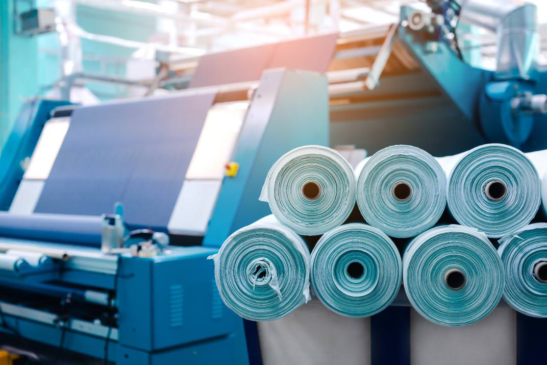 Rollen von Polyesterstoffen bei der Herrstellung in einer Fabrik.