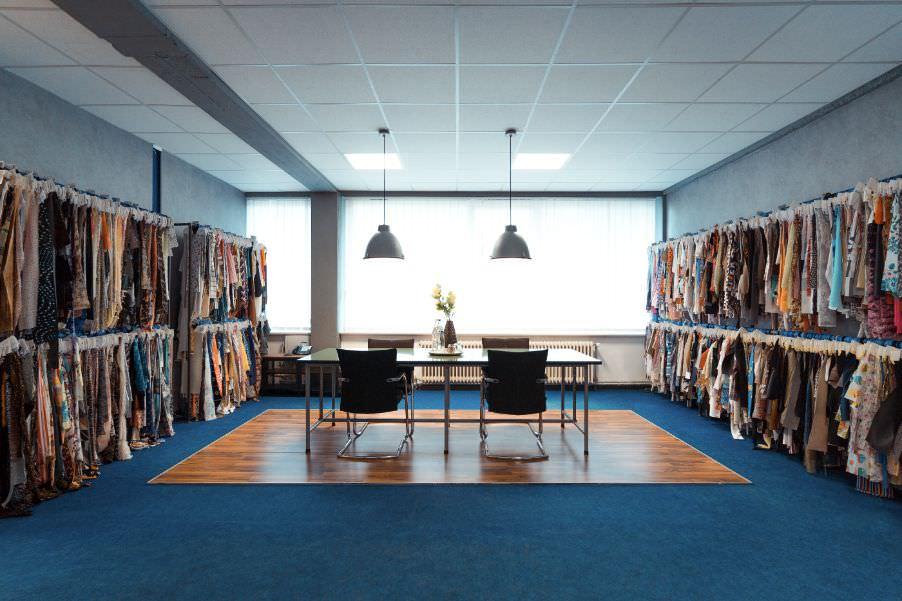 Der Showroom mit über 8.000 Stoffproben. Sie sehen einen Tisch mit 4 Stühlen, umrahmt von Kleiderständern voller Stoffproben