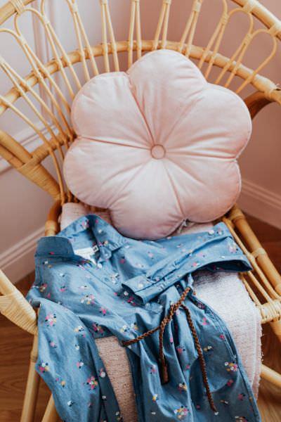 Ein Baumwollkleid aus Kinderstoff und ein Blumenkissen auf einem Korbstuhl
