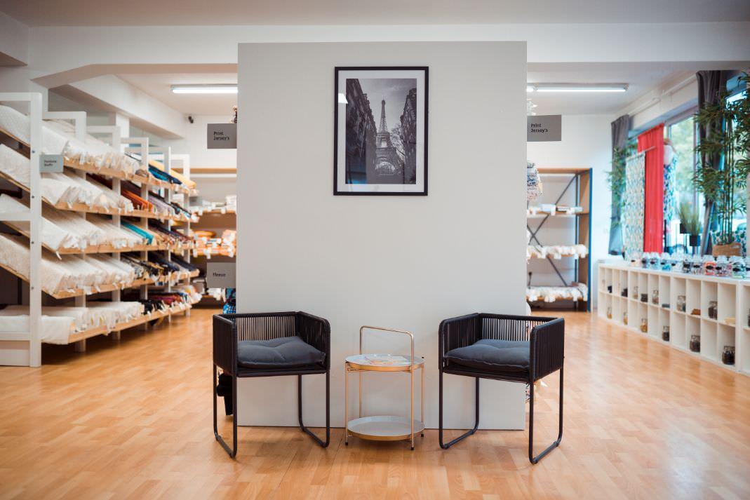 Willkommen im Showroom! Hier sehen Sie zwei Stühle, die Fensterwand und Stoffe vom Showroom
