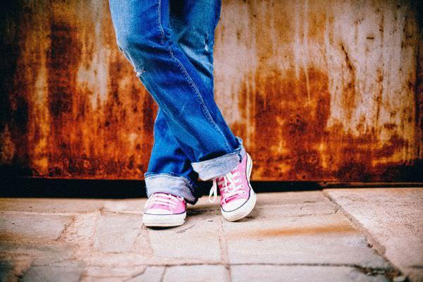 Eine Frau in Ripped Jeans in dunklem Blau und rosa Sportschuhen