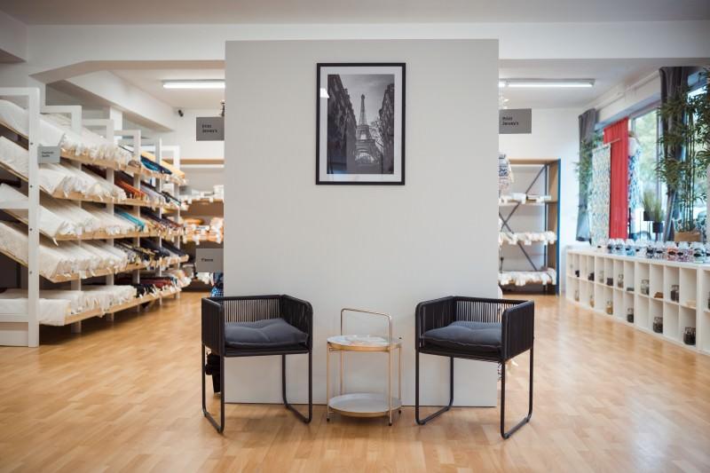 Der Übergang vom Showroom zum Lagerverkauf: Stühle zum Hinsetzen, Nähzubehör und Regale voller Stoffe auf Rollen sehen Sie hier