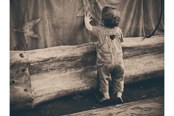 Kleinkind in einer jeans latzhose spielt vor einem vorhang