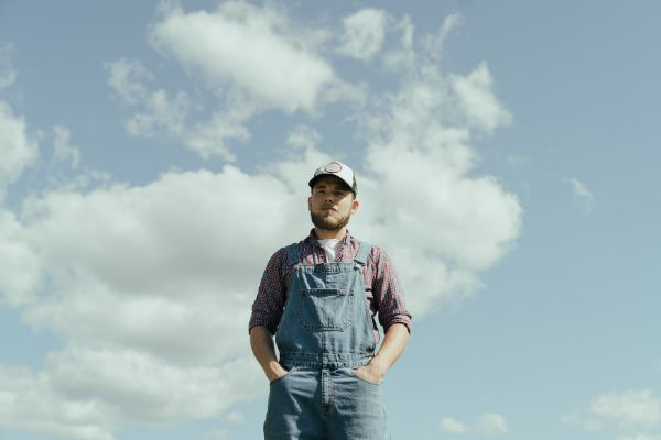 Amerikanischer Farmer in einer Jeans Latzhose und Basecap vor blauem Himmel