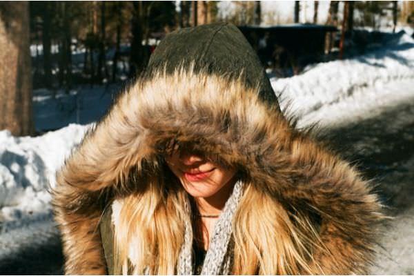 junge_frau_trägt-einen_wintermantel_mit_kunstfell_abschluss
