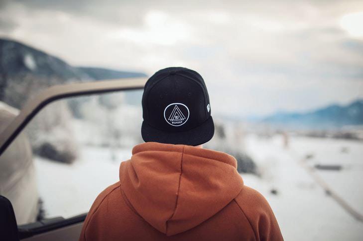 Ein Mann mit einem orangen Hoodie steht vor einer Schneelandschaft.