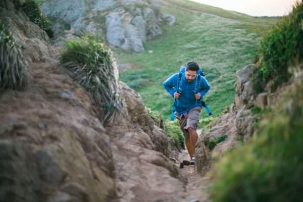 Mann in blauer Fleece-Jack mit Rucksack wandert in den Bergen