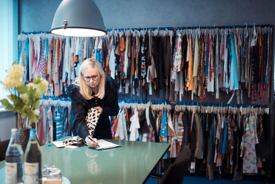 Eine Mitarbeitern steht vor Kleiderstangen voller Stoffproben und schaut auf Notizen auf einem Tisch vor ihr.