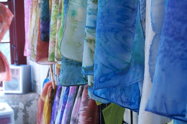 Bunte Tücher aus Seidenchiffon hängen an einer Stange