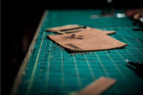 Kunstleder wird auf einer Schneidermatte zurecht geschnitten
