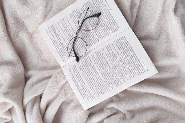 Kuscheldecke aus Fleece unter einem aufgeschlagenem Buch und einer abgesetzten Brille