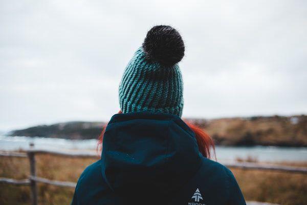 Frau an der Nordseeküste mit Kapuzenjacke und Wollmütze mit einer Bommel aus Kunstfell.