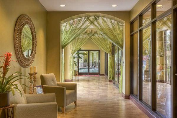 Sehr helle Hotellobby mit grünen Dekovorhängen